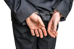 Arrested businessman in handcuffs with hands behind back. Isolated on white background Royalty Free Stock Photography