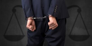 Arrested man with balance on the background. Arrested businessman in handcuffs with hands behind back and justice symbol wallpaper Stock Images