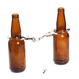 Arrested Drunk. Concept image of getting arrested while being drunk, shown with two beer bottles with handcuffs on Stock Photography