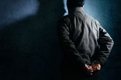 Arrested male criminal with handcuffs facing prison wall stock photography