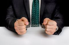 Arrested man in black suit with handcuffs. In police station Stock Photos