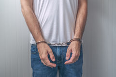 Arrested man with cuffed hands in front Stock Photo