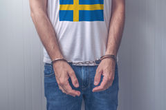 Arrested man with cuffed hands wearing shirt with Swedish flag Stock Photo
