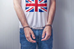 Arrested man with cuffed hands wearing shirt with UK flag Stock Photos