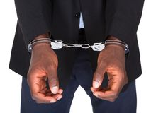 Arrested man with handcuffed hands. African Man With Handcuffed Hands Isolated On White Background Stock Photo