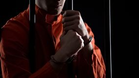 Arrested man in handcuffs behind bars feeling angry about failed robbery plan royalty free stock photography