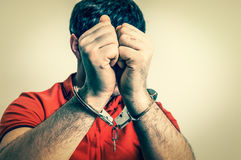 Arrested man in handcuffs hidden his face - retro style Stock Photos