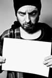 Arrested man thief holding blank board. Portrait of arrested man holding a blank sheet Royalty Free Stock Photo