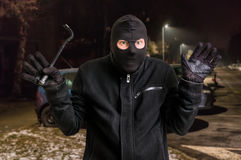 Arrested masked thief in balaclava with crowbar and raised arms Royalty Free Stock Image