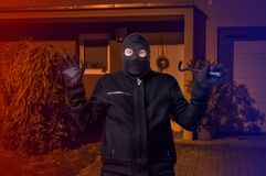 Arrested masked thief in balaclava with crowbar and raised arms. At night Royalty Free Stock Images