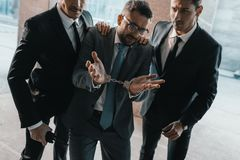 Arrested offender showing security guards shrug. Gesture stock photography