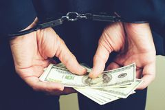 Arrested official in handcuffs counting dollar banknotes. Concept of fraud, detention, crime and bribery, toned image royalty free stock photography