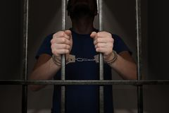Arrested prisoner is holding bars in prison cell.  Royalty Free Stock Photo