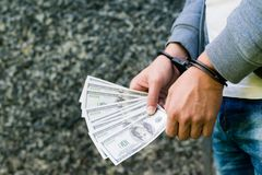 Arrested rowdy in handcuffs counting dollar banknote. Arrested f royalty free stock photography