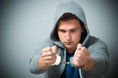 Arrested teenager with handcuffs. On his hands Stock Photos