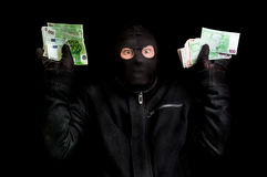 Arrested thief in balaclava with stolen money and raised arms Stock Photos