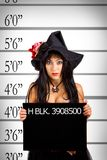 Arrested witch. Mugshot of pretty witch in police station royalty free stock image