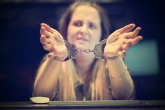Criminal hands locked in handcuffs. Arrested woman handcuffed hands. Close-up of office worker, Prisoner or arrested terrorist, hacker, bribetaker, close-up of stock images