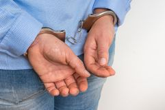 Arrested woman in handcuffs with hands behind back. On white background royalty free stock images