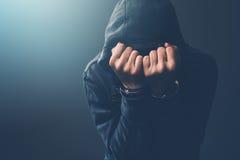 Arresterad datoren hacker med handbojor som bär det med huva omslaget Royaltyfri Fotografi