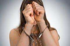 Arresterad kvinna i handbojor som döljas hennes framsida Fotografering för Bildbyråer