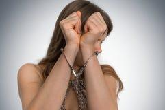 Arresterad kvinna i handbojor som döljas hennes framsida Royaltyfria Bilder