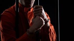 Arresterad man i handbojor bak stänger som känner sig ilskna om missat röveriplan royaltyfri fotografi