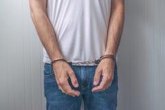 Arresterad man med örfilade upp händer framme Arkivfoto