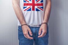 Arresterad man med örfilade upp händer som bär skjortan med UK-flaggan Arkivfoton