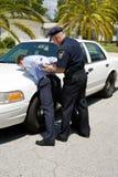 Arresting Drunk Driver. Police officer placing a drunk driver under arrest Royalty Free Stock Image