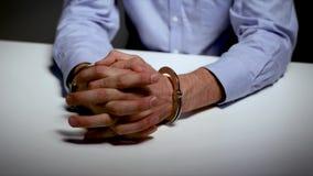 Arresto - mani con le manette sulla tavola stock footage