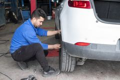 Arrière changeant mécanique de pneu d'une voiture blanche photographie stock