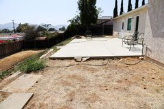 Arrière-cour avec la dalle de patio et les mauvaises herbes et la maison de stuc image libre de droits