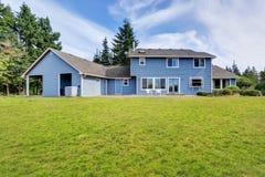 Arrière-cour bleue de maison avec le secteur concret de patio de plancher et le jardin soigné photos stock