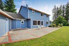 Arrière-cour bleue de maison avec le secteur concret de patio de plancher et le jardin soigné images stock