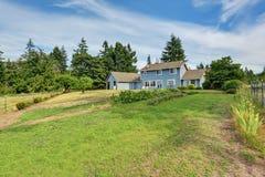 Arrière-cour bleue de maison avec le secteur concret de patio de plancher et le jardin soigné photo stock