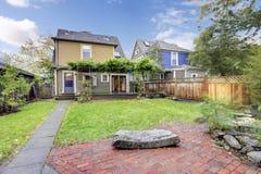 Arrière-cour clôturée avec la pelouse, le passage couvert couvert et la terrasse ouverte Image libre de droits
