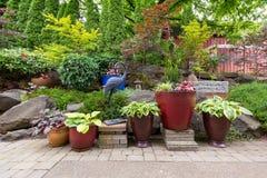 Arrière-cour de jardin aménageant en parc avec des usines et des machines à paver de pierre images stock