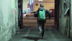 Arrière d'homme courant avec le sac à dos vert hors de la cour Il courent sur la droite clips vidéos