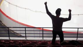 Arrière d'une fan d'hockey sur la tribune, qui saute et se lève des handes Mouvement lent clips vidéos