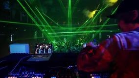 Arrière de deux DJ au mélangeur du DJ dans la boîte de nuit serrée Mouvement lent clips vidéos