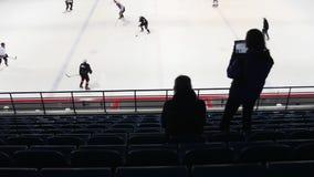 Arrière de deux fans d'hockey sur la tribune observant le jeu Mouvement lent banque de vidéos