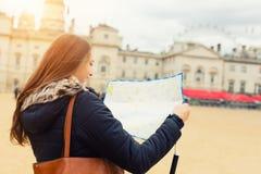 Arrière de jeune femme de voyageur recherchant la direction sur la carte Photographie stock libre de droits