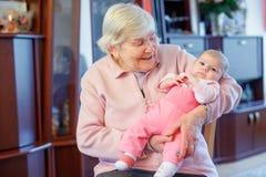 Arrière grand-mère tenant l'petit-enfant nouveau-né de bébé sur le bras photos libres de droits