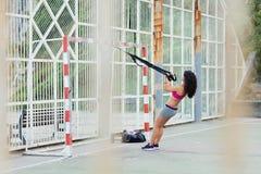 Arricci per l'allenamento del bicipite di forma fisica con le cinghie del trx Fotografia Stock