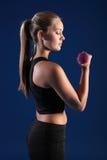 Arricciatura di Bicep dalla bella giovane donna di forma fisica Fotografia Stock