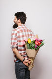 Arrière de jeune homme beau avec la barbe et bouquet gentil des fleurs Photo stock