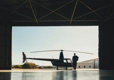 Arrivée pilote à l'aéroport avec un hélicoptère dans le hangar Photo libre de droits