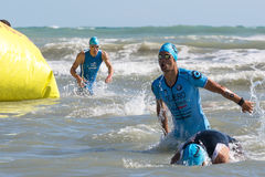 Arrival of the first athletes at the end of the swimming test at Ironman 70.3 in Pescara. Pescara, Italy - June 18, 2017: Arrival of the first athletes at the Stock Photography