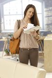 Arrival at home. Young woman looking at mail while arriving at home royalty free stock images